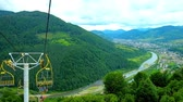 chairlift : Panorama of Carpathian mountains from the ski lift of Makovytsia Mount, Mizhhiria settlement is seen in valley of Rika river behind the lush mountain forests, Ukraine.