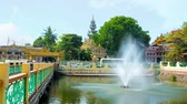 dagon : Fountain in pond of Mahavijaya (Maha Wizaya) Pagoda with a bridge and pyatthat roof of Kyauk Sein Image House behind the trees, on February 17 in Yangon.