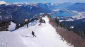 ski piste : ST GILDEN, AUSTRIA - FEBRUARY 23, 2019: Amazing view from the peak of Zwolferhorn mountain with rocky Alps, Wolfgangsee lake and skiers, going downhill the snowy slope, on February 23 in St Gilden Stock Footage