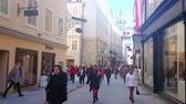 úzký : SALZBURG, AUSTRIA - FEBRUARY 27, 2019: Enjoy the shopping in crowded Getreidegasse street with historic guild signs over the stores and Rathaus tower on background, on February 27 in Salzburg. Dostupné videozáznamy