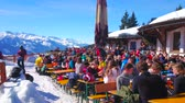veranda : ZELL AM SEE, AUSTRIA - FEBRUARY 28, 2019: Crowded open air terrace of the lounge cafe, located on snowy Areitalm Alpine meadow, sportsmen take a rest after the downhill, on February 28 in Zell Am See.