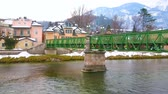 mesire : The view on the old bridge across the fast flowing Traun river, scenic mansions on its bank and snowy Alps on the background, Bad Ischl, Salzkammergut, Austria.