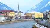 parroquia : BAD ISCHL, AUSTRIA - FEBRUARY 20, 2019: The riverside cityscape with historical housing, tall belfry of Parish church, stone banks of Traun river and snowy Alps, on February 20 in Bad Ischl Archivo de Video