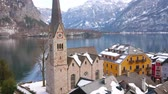 parroquia : Hallstatt town center with a view on Evangelical Parish Church, old townhouses, embankment of Hallstatter see (lake) and snowy Dachstein Alps on the background, Salzkammergut, Austria.