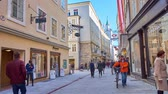 úzký : SALZBURG, AUSTRIA - FEBRUARY 27, 2019: Daily activity in Getreidegasse shopping street with many stores and boutiques, located in old edifices and a view on Rathaus tower, on February 27 in Salzburg. Dostupné videozáznamy