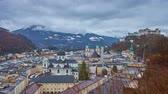 conservar : The cityscape of medieval Salzburg on rainy day, with a view on heavy clouds, hovering above the Alps and the Hohensalzburg fortress dominating the Altstadt (old town), Austria.