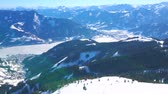 on piste : Enjoy magnificent Alpine landscape from the top of Schmitten mount with a view on Zell am See resort, frozen Zeller see (lake) and futuristic cabin of Schmittenhohenbahn cable car, Austria.