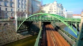 bairro : VIENNA, AUSTRIA - FEBRUARY 18, 2019: Construction of Zollamtsbrucke railway bridge over Wienfluss river with riding metro (U-Bahn) train and pedestrian Zollamtssteg above it, on February 18 in Vienna.