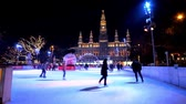 viyana : VIENNA, AUSTRIA - FEBRUARY 18, 2019: The evening Rathaus square with a view on crowded ice skating rink in front of brightly illuminated Town Hall (Rathaus), on February 18 in Vienna. Stok Video