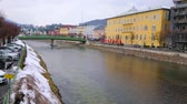 konak : BAD ISCHL, AUSTRIA - FEBRUARY 20, 2019: Historic mansions of old town stretch along the banks of Traun river, crossed by colorful metal bridges, on February 20 in Bad Ischl.