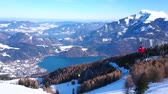 持ち上げ : Zwolferhorn mount is nice place to watch rocky Alps, bright blue Wolfgangsee lake and retro cabins of cable car, running along snowy slope, covered with ski trails, St Gilden, Salzkammergut, Austria. 動画素材