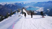 ski piste : ST GILDEN, AUSTRIA - FEBRUARY 23, 2019: The peak of Zwolferhorn mount is best place to overlook Wolfgangsee lake, Alpine scenery and watch the skiers on downhill, on February 23 in St Gilden Stock Footage