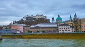 Walk along the bank of Salzach river with a view on the main city landmarks - Salzburg castle on the Festunsberg hilltop, dome of Cathedral and historic mansions, Austria.