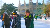 viyana : VIENNA, AUSTRIA - FEBRUARY 17, 2019: Rathaus square in front of historical Town Hall is occupied with large multilevel ice skating rink, full of kids, youth and families, on February 17 in Vienna. Stok Video