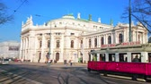 viyana : VIENNA, AUSTRIA - FEBRUARY 17, 2019: The bright red vintage tram drives along the busy Universitatsring avenue in front of historical Burgtheater (theatre), on February 17 in Vienna.