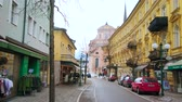 BAD ISCHL, AUSTRIA - FEBRUARY 20, 2019: Franz Joseph Strasse with scenic historic edifices, tourist stores, cafes and St Nicholas Parish Church on background, on February 20 in Bad Ischl 動画素材