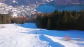 Spectacular view from the cable car on the Zwolferhorn mountain slope, skiers, going uphill, coniferous forest, Alps and deep blue Wolfgangsee lake in valley, St Gilden, Salzkammergut, Austria.