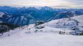 Enjoy winter mountain landscape from the slope of Feuerkogel mount with a view on the maze of pistes, numerous skiers, riding chairlift and foggy Dachstein Alps on background, Salzkammergut, Austria.