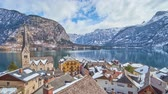 konak : The view on the old town center with historical housing, Evangelical Parish church and ferry, floating along Hallstattersee lake, Hallstatt, Salzkammergut, Austria. Stok Video