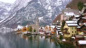 The bank of Hallstatter see is occupied with dense colorful houses, stone Parish church with tall spire and snowy Dachstein Alps on background, Hallstatt, Salzkammergut, Austria.