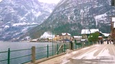 HALLSTATT, AUSTRIA - FEBRUARY 21, 2019: Seestrasse is the lakeside promenade and center of tourist activity in town, people enjoy  Hallstatter see and visit local stores, on February 21 in Hallstatt.