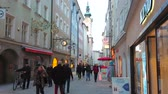 úzký : SALZBURG, AUSTRIA - FEBRUARY 27, 2019: The crowded Linzergasse street with many stores, cafes, art galleries, historic edifices and belfry of St Sebastian church, on February 27 in Salzburg. Dostupné videozáznamy