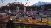 The evening cityscape of old Salzburg in dimmed lights from the Kapuzinerberg hill, located opposite the Hohensazburg Castle, dominating the city skyline, Austria. 動画素材