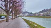 SALZBURG, AUSTRIA - MARCH 1, 2019: Walk along the park in Elisabethkai embankment of Salzach river with a view on Hohensalzburg Fortress, towering the Altstadt (old town), on March 1 in Salzburg