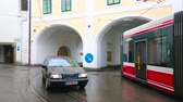 GMUNDEN, AUSTRIA - FEBRUARY 22, 2019: The modern tram drives through the arch of K-Hof (Kammerhofmuseen) building to the Traunbrucke bridge, on February 22 in Gmunden.