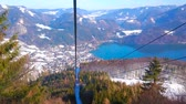 Ride the vintage Zwolferhorn cable car and observe the landscape of Salzkammergut, mountain lake of Wolfgangsee, lush coniferous forests on snowy slope, St Gilden, Austria.