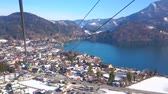 The cable car journey to Zwolferhorn mountain top over the tourist village of St Gilden and scenic Wolfgangsee lake, Salzkammergut, Austria. 動画素材