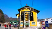 下段 : ST GILDEN, AUSTRIA - FEBRUARY 23, 2019: The colorful vintage booths of Zwolferhorn cable car arrive and departure from its lower station, on February 23 in St Gilden