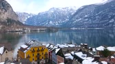HALLSTATT, AUSTRIA - FEBRUARY 21, 2019: Watch the mirror surface of Hallstattersee lake, rocky Dachstein Alps and tall spire of Parish Church over the old town roofs, on February 21 in Hallstatt. 動画素材