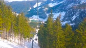 GOSAU, AUSTRIA - FEBRUARY 26, 2019: Panorama Jet Zwieselalm cable car offers picturesque vistas on Alpine landscapes, small Gosaub lake in valley and lush fir forests, on February 26 in Gosau