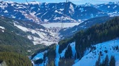ZELL AM SEE, AUSTRIA - FEBRUARY 28, 2019: Schmittenhohenbahn cable car breath-taking journey with a view on Alpine snowy slopes, pistes, forests and frozen Zeller see, on February 28 in Zell Am See