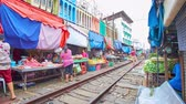 禁止 : MAEKLONG, THAILAND - MAY 13, 2019: The train slowly rides along the narrow alley of Maeklong Railway Market, lined with fresh vegetables and fruits stalls, tiny cafes and shops, on May 13 in Maeklong 動画素材