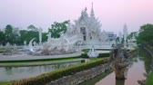 скульптура : Visit White Temple (Wat Rongkhun) on sunset and enjoy its unique architecture in dimmed purple colors of the evening sky, Chiang Rai, Thailand