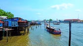 chao phraya : BANGKOK, THAILAND - APRIL 22, 2019: Fast and chaotic boat traffic on Chao Phraya river with a view on the old shabby neighborhood of wooden stilt huts along the bank, on April 22 in Bangkok Stock Footage