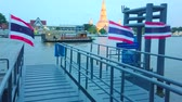 Чеди : BANGKOK, THAILAND - APRIL 22, 2019: The view on Wat Arun Temple in evening lights behind the Chao Phraya river with floating ships, barges and pontoon pier with flags, on April 22 in Bangkok