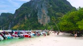 PHIPHI DON, THAILAND - APRIL 27, 2019: The Tonsai Bay of Phi Phi Don Island with line of speed boats, moored along the white sandy shore and the tall rocks on the background, on April 27 in PhiPhi Don Vídeos