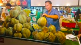 AO NANG, THAILAND - APRIL 27, 2019: The stall of Ao Nang Night Market with heap of durians, the merchant checks the fruits ripeness, knocking their thorny rind with a stick, on April 27 in Ao Nang