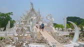 скульптура : CHIANG RAI, THAILAND - MAY 9, 2019: Tourists enter the bridge of rebirth cycle of White Temple (Wat Rongkhun), guarded by giant Kinnaree guards, on May 9 in Chiang Rai