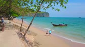 AO NANG, THAILAND - APRIL 25, 2019: Watch golden sandy Ao Nang beach with longtail boats from the shady seaside promenade of resort, lined with lush green fig trees, on April 25 in Ao Nang Vídeos