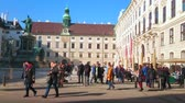 konak : VIENNA, AUSTRIA - FEBRUARY 17, 2019: The crowd of tourists walks along the monument of Kaiser Franz I, located in In Der Burg courtyard of Hofburg Palace, on February 17 in Vienna. Stok Video