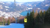 Observe the Alpine landscape from the retro gondola of Zwolferhorn cableway, riding along the snowy slope from the valley of Wolfgangsee lake to the mountain top, St Gilden, Salzkammergut, Austria