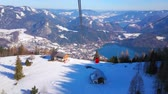 ski piste : Watch the Alpine landscape of St Gilden and Wolfgangsee valley from the swinging gondola of Zwolferhorn cableway on the windy weather, Salzkammergut, Austria Stock Footage