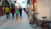 úzký : SALZBURG, AUSTRIA - FEBRUARY 27, 2019: The parked bicycle at the postcard stand of souvenir store in crowded Linzergasse street, on February 27 in Salzburg. Dostupné videozáznamy