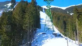 ski piste : The snowy slope of Schmitten mount with lush pine forests, ski trails and riding gondolas of Trassxpress cableway, Zell am See, Austria Stock Footage