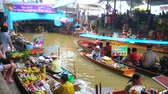 comerciantes : DAMNOEN SADUAK, THAILAND - MAY 13, 2019: Walk along the klong bank of Ton Khem floating market with many sampans (boats) with fresh fruits, snacks, local dishes and drinks, on May 13 in Damnoen Saduak