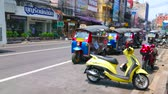 khaosan : BANGKOK, THAILAND - APRIL 22, 2019: The slow traffic along the Charkrapong Road with parked tuk tuks and scooters, lined with shops and cafes of Banglampoo tourist district, on April 22 in Bangkok Stock Footage